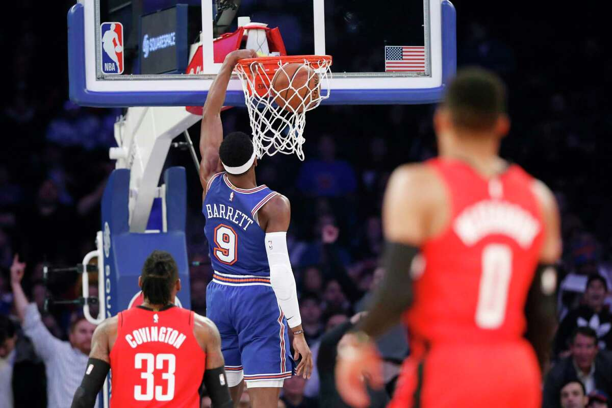 Houston Rockets forward Robert Covington (33) and guard Russell Westbrook (0) watch as New York Knicks guard RJ Barrett (9) dunks during the second quarter of an NBA basketball game in New York, Monday, March 2, 2020. (AP Photo/Kathy Willens)