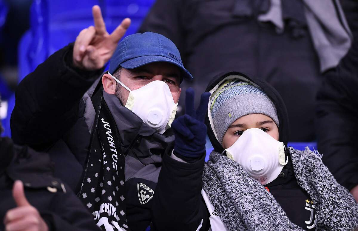 TOPSHOT - Juventus supporters wear protective face masks as a safety measure against the COVID-19 novel coronavirus at the Parc Olympique Lyonnais stadium in Decines-Charpieu, central-eastern France, on February 26, 2020, ahead of the UEFA Champions League round of 16 first-leg football match between Lyon and Juventus. (Photo by FRANCK FIFE / AFP) (Photo by FRANCK FIFE/AFP via Getty Images)
