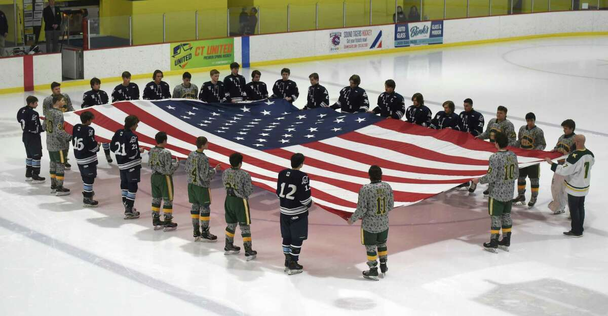 Players on the Trinity Catholic and Wilton boys ice hockey teams display an American flag during the national anthem before the start of their game at Terry Conners Rink on Monday. The Crusaders retired the No. 24 jersey of former player Brian Bill, a Navy SEAL who died in Afghanistan on Aug. 6, 2011.