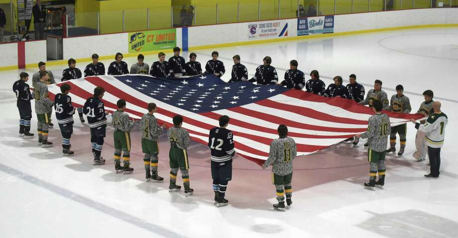 Players on the Trinity Catholic and Wilton boys ice hockey teams display an American flag during the national anthem before the start of their game at Terry Conners Rink on Monday. The Crusaders retired the No. 24 jersey of former player Brian Bill, a Navy SEAL who died in Afghanistan on Aug. 6, 2011. Photo: Dave Stewart / Hearst Connecticut Media / Hearst Connecticut Media