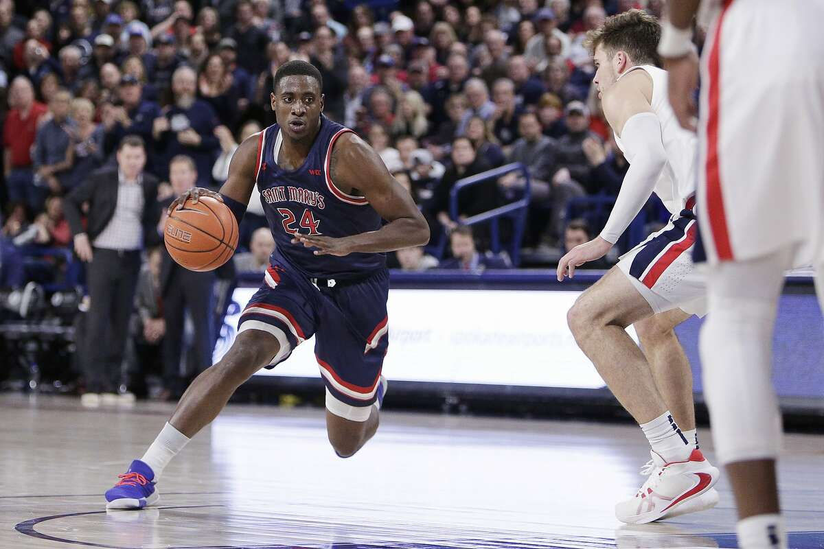 Saint Mary's forward Malik Fitts, left, dribbles the ball while defended by Gonzaga forward Corey Kispert during the second half of an NCAA college basketball game in Spokane, Wash., Saturday, Feb. 29, 2020. (AP Photo/Young Kwak)