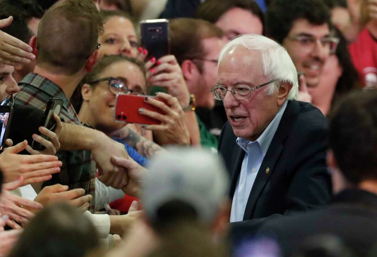 FILE - In this Sunday, Feb. 16, 2020, file photo, Democratic presidential candidate Sen. Bernie Sanders, I-Vt., right, poses for a photograph with a supporter after a campaign stop in Denver.