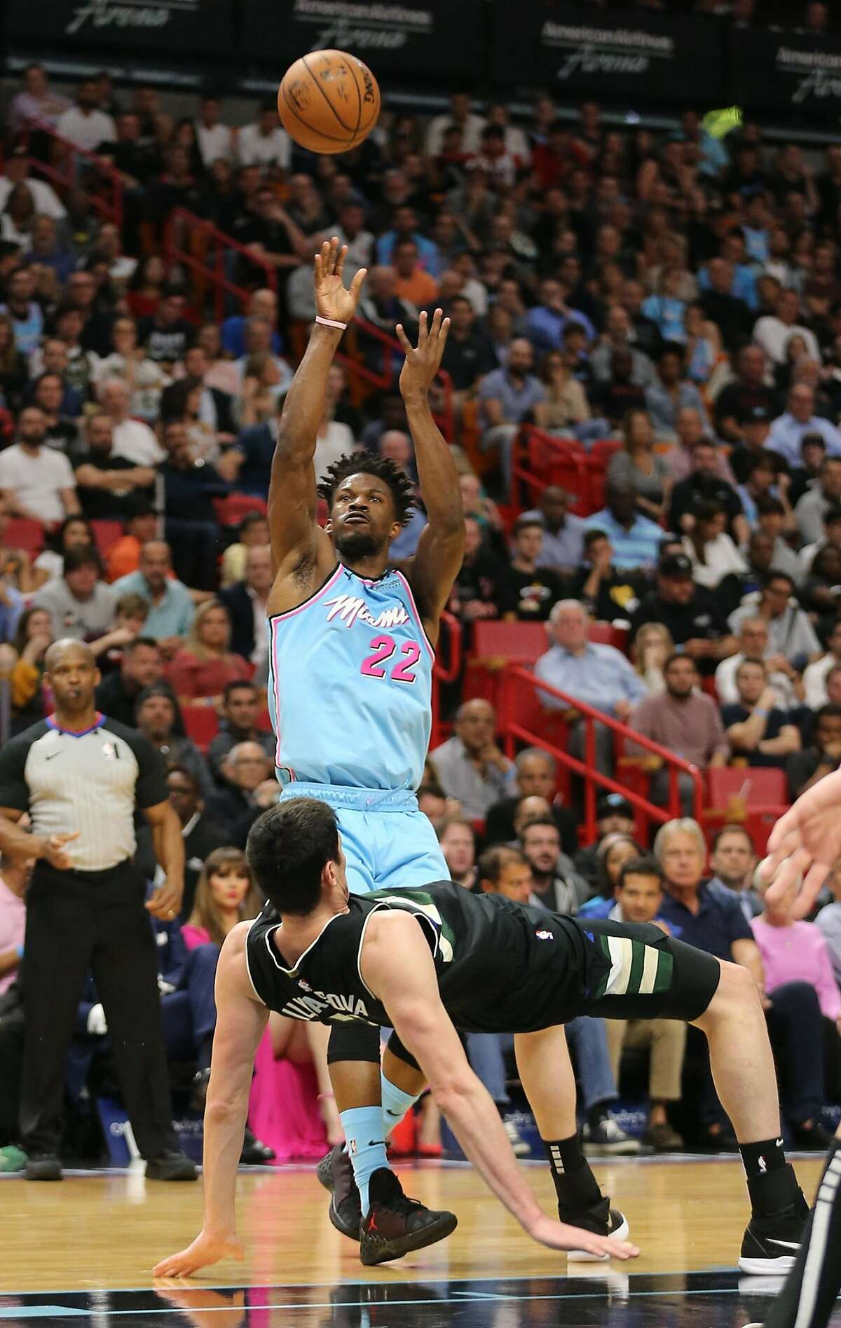 Miami Heat's Jimmy Butler (22) shoots over Milwaukee Bucks' Ersan Liyasova (77) in the fourth quarter at the AmericanAirlines Arena on March 2, 2020 in Miami. The Heat won, 105-89. (Charles Trainor Jr./Miami Herald/TNS)
