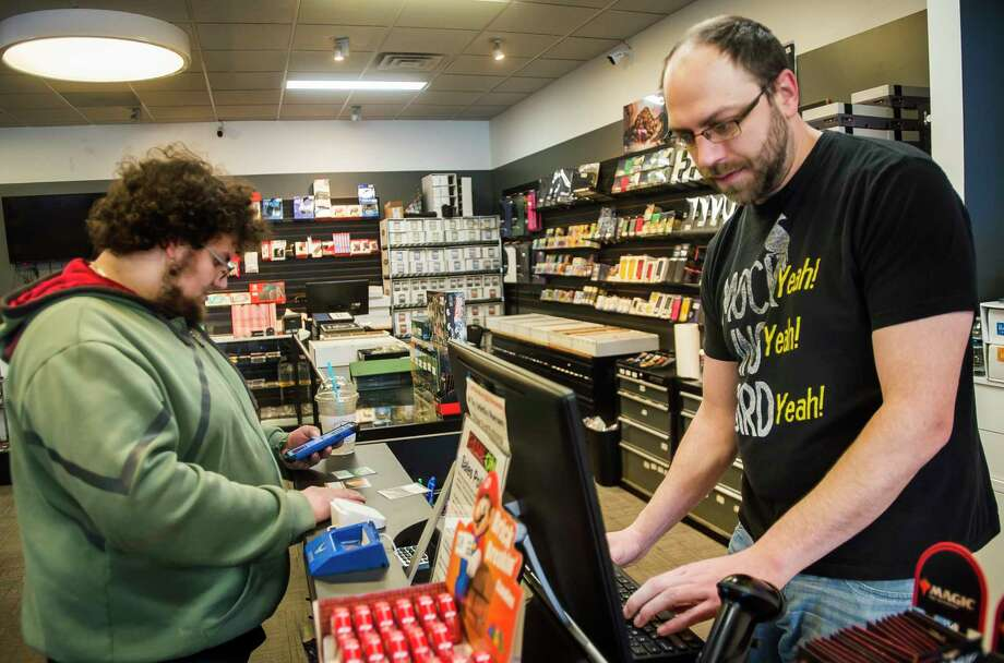 Tyler Smith, left, purchases playing cards from Game On manager Joe Dempsey, right, before playing a game of Magic: The Gathering with friends Monday, March 2, 2020 at the store, which recently moved to 814 S. Saginaw Road. (Katy Kildee/kkildee@mdn.net)