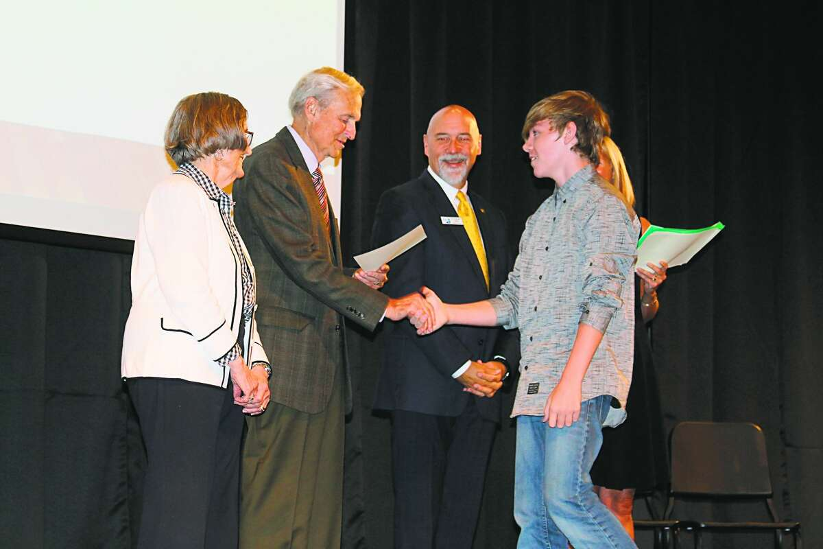 Bill Paine shakes hands with a student during a scholarship induction ceremony. Paine helped found the Manistee Commitment Scholarship to provide area students with the opportunity of a full-ride to West Shore Community College.