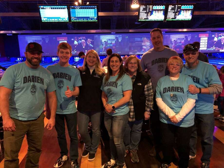 Cops & Kids headed to Bowlmor in Norwalk recently, including Officer Dan Ehret, left, Nikolas Kunz, First Selectman Jayme Stevenson, Lt. Alison Hudyma, Janice Marzano, Captain Jeremiah Marron, Chief Donald Anderson and his wife, Georgia. Photo: Contributed /