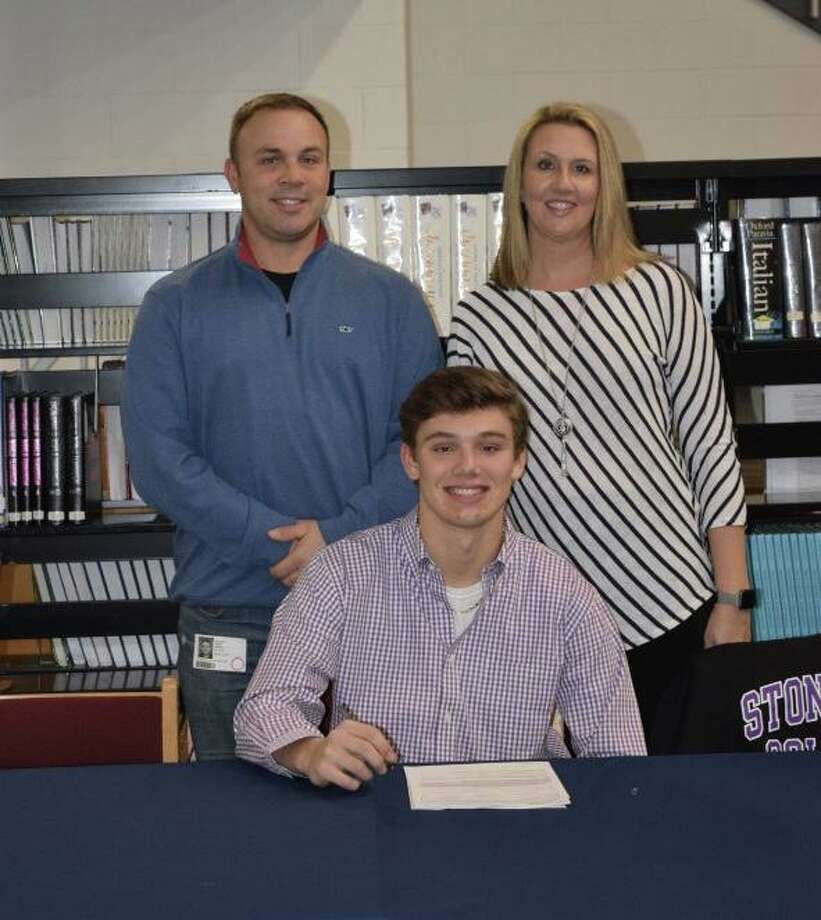 Foran High's Andrew Janik, with his father Jeff and mother Lauren, signs his letter of intent to play football at Stonehill College. Photo: Contributed Photo / MaryGrace Weissauer / Milford Mirror