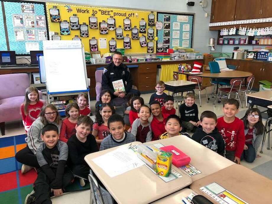 Police, fire and emergency medical personnel read to students at Long Hill School on Monday, March 2, for Read Across America Day. Photo: Contributed Photo / Connecticut Post