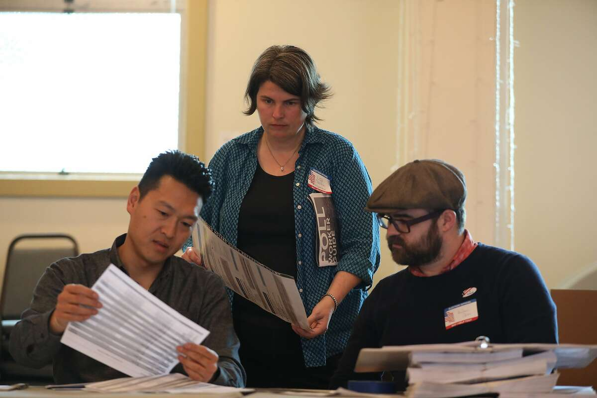 From left to right: Mike Chung, poll worker, Lisa Claxton, precinct inspector, and Andrew Seko, poll worker, view paperwork at Our Lady of Lourdes Church during Election Day in Oakland, Calif., on Tuesday, March 3, 2020. Super Tuesday brings a look at California's fairly new rules allowing people to change party registration on Election Day.