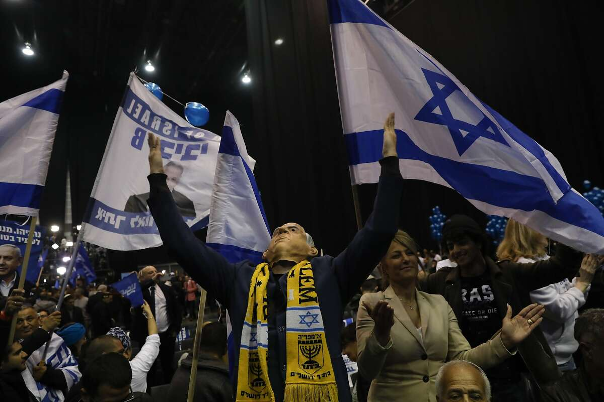 A supporter of Israeli Prime Minister Benjamin Netanyahu wear mask with his likeness as they celebrate first exit poll results for the Israeli elections at his party's headquarters in Tel Aviv, Israel, Monday, March 2, 2020. (AP Photo/Ariel Schalit)