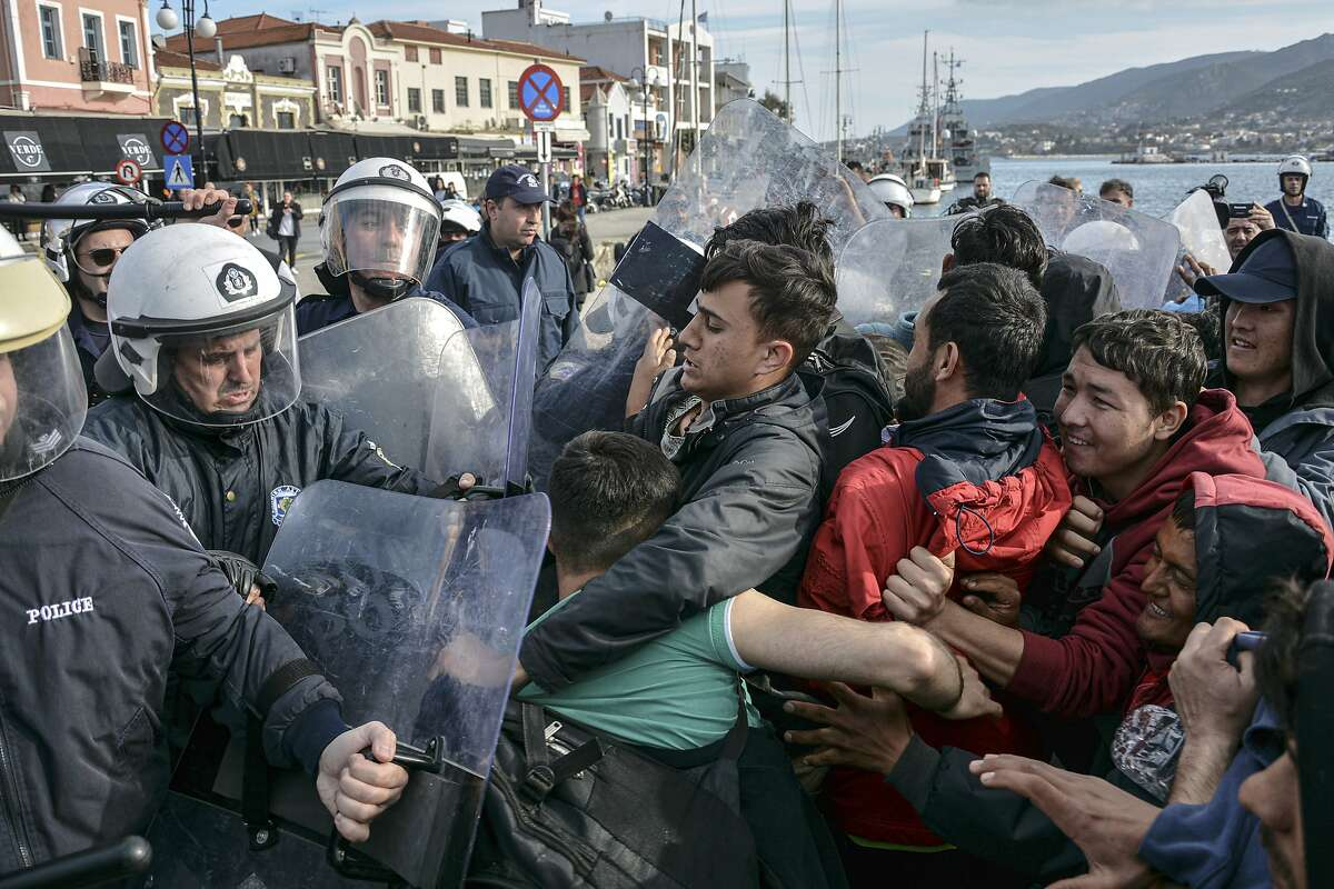 Migrants scuffle with Grek police at the port of Mytilene after locals block access to the Moria refugee camp, on the northeastern Aegean island of Lesbos, Greece, on Tuesday, March 3, 2020. Migrants and refugees hoping to enter Greece from Turkey appeared to be fanning out across a broader swathe of the roughly 200-kilometer-long land border Tuesday, maintaining pressure on the frontier after Ankara declared its borders with the European Union open. (AP Photo/Panagiotis Balaskas)
