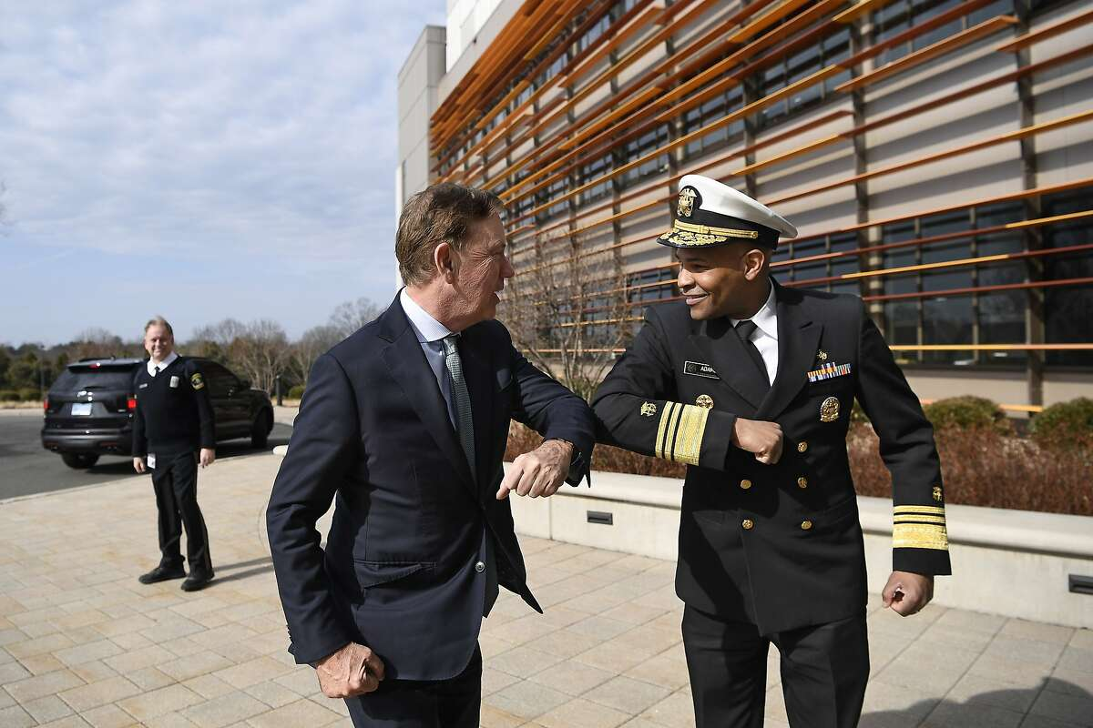 U.S. Surgeon General Vice Admiral Jerome M. Adams, right, bumps elbows with Connecticut Gov. Ned Lamont as they meet for a visit at the Connecticut State Public Health Laboratory, Monday, March 2, 2020, in Rocky Hill, Conn. The Surgeon General is encouraging people to bump elbows rather than shaking hands or fist bumps to help prevent the spread of COVID-19. (AP Photo/Jessica Hill)