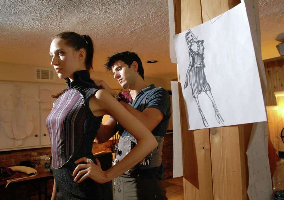 Fashion designer Jason Troisi, right, fits his Cobra Infinity dress on model Tanya Sinkevica of New York City, in the studio of his Cos Cob home, August 17, 2010. Photo: Bob Luckey / Greenwich Time