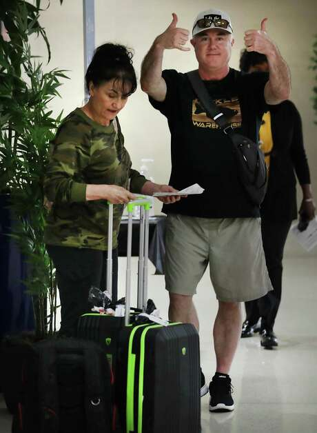 A man and a woman, both evacuees from the coronavirus-infected Diamond Princess cruise ship in Japan, give thumbs up Tuesday, March 3, 2020, after using hand sanitizer as they arrived at San Antonio International Airport from Joint Base San Antonio-Lackland where they had been quarantined. Photo: Bob Owen /San Antonio Express-News / San Antonio Express-News