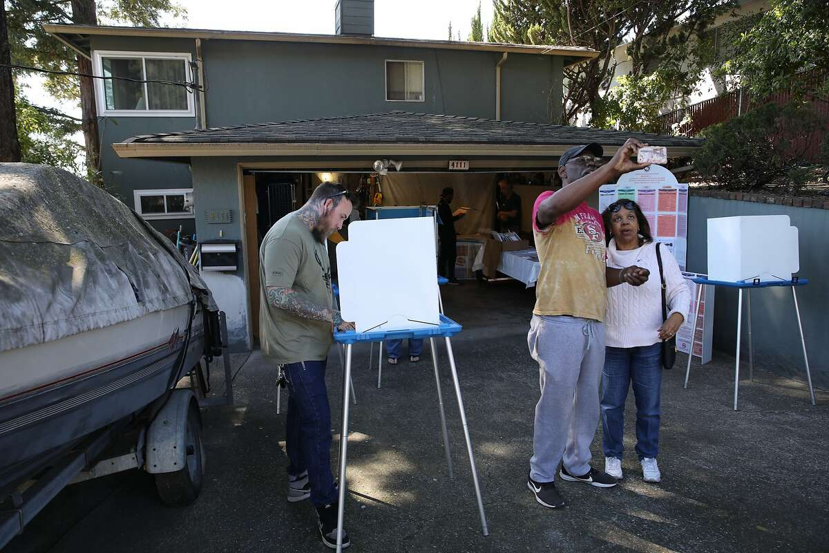 Joseph Parker, left, votes while Donald and Regina Walker, all of Oakland, shoot a selfie after casting their votes during Election Day at a garage, located in the 4100 block of Harbor View Ave., in Oakland, Calif., on Tuesday, March 3, 2020. Super Tuesday brings a look at California's fairly new rules allowing people to change party registration on Election Day.