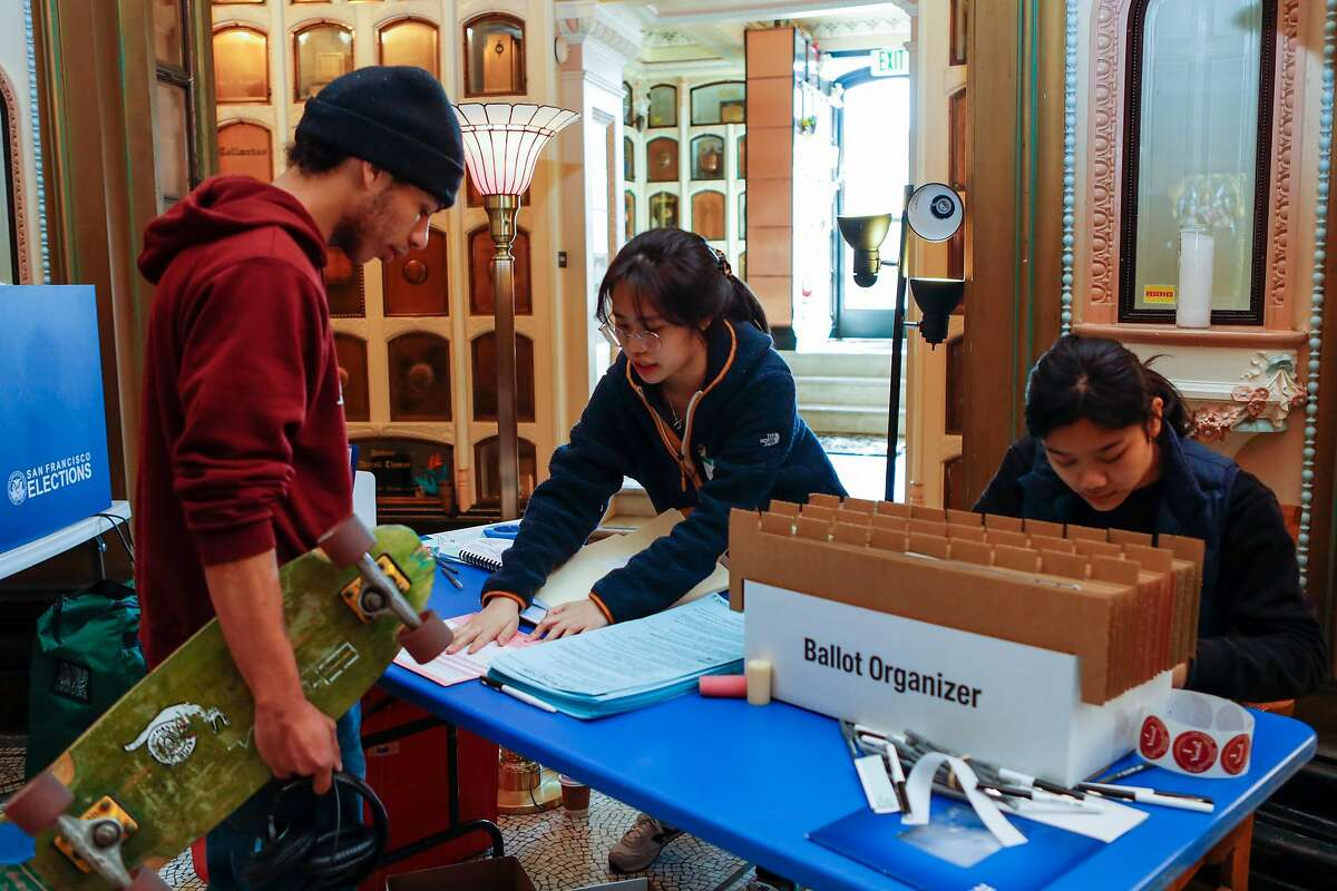 Poll workers Haley Feng (center) and Dolkar Nyshang, assist Jeremy Sullivan in retrieving his ballot before casting his vote at San Francisco Columbarium on Tuesday, March 3, 2020, in San Francisco, Calif.