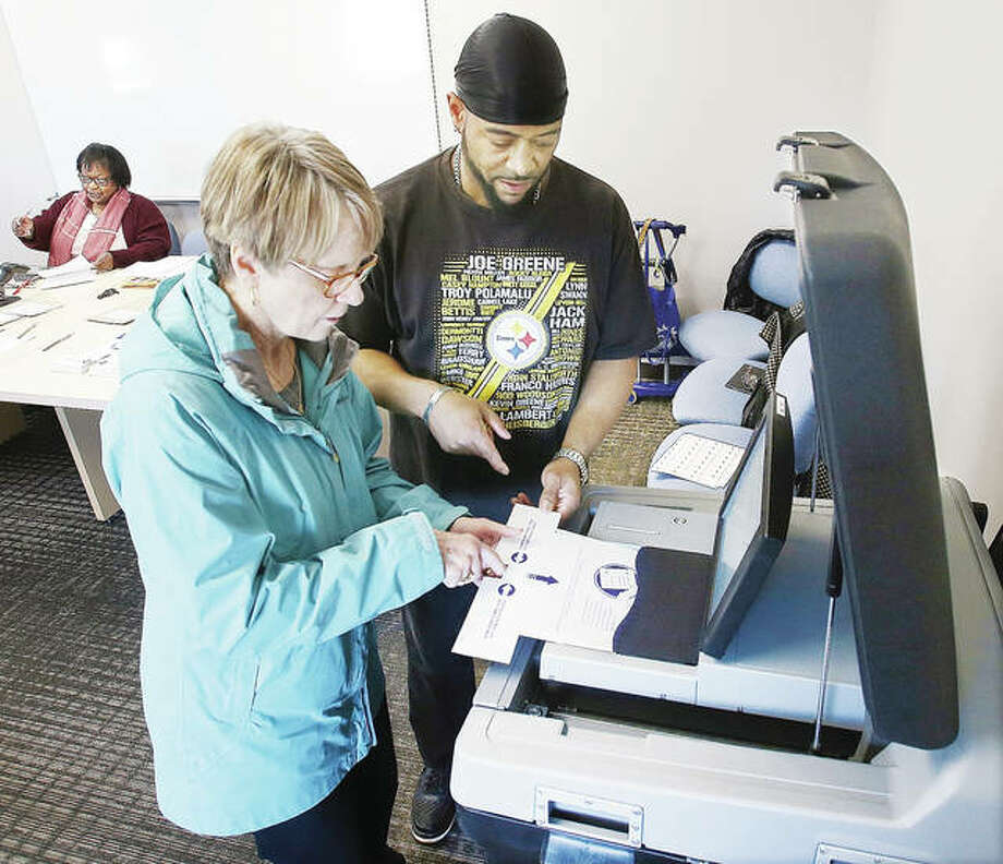 Carol Redd, of Alton, left, feeds her ballot into the tabulation machine Tuesday at the Scott Bibbs Center in Alton as election judge Delano Ross supervises. Early voting in Illinois began Monday with 11 polling locations now open in Madison County for the March 17 primary.