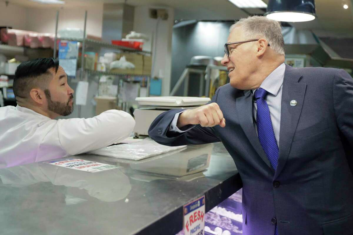 Washington Gov. Jay Inslee, right, bumps elbows with a worker at the seafood counter of the Uwajimaya Asian Food and Gift Market, Tuesday, March 3, 2020, in Seattle's International District. Inslee said he's doing the elbow bump with people instead of shaking hands to prevent the spread of germs, and that his visit to the store was to encourage people to keep patronizing businesses during the COVID-19 Coronavirus outbreak. Earlier in the day, following a tour at a health clinic, Inslee urged people to wash hands frequently and practice other measures of health hygiene, and to stay home from work and public events if they don't feel well or have any symptoms of illness. (AP Photo/Ted S. Warren)