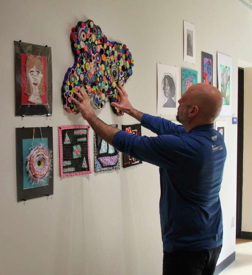 WSCC associate professor of arts Eden Foley hangs one of the 111 pieces of art that are on display at the college's Regional High School Art Show. (Ken Grabowski/News Advocate)