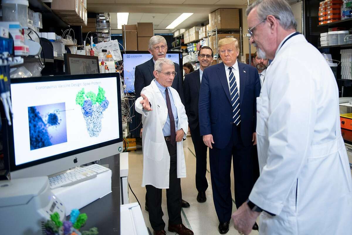 National Institute of Allergy and Infectious Diseases Director Tony Fauci (left) speaks to President Donald Trump during a tour of the National Institutes of Health's Vaccine Research Center on March 3, 2020, in Bethesda, Md,
