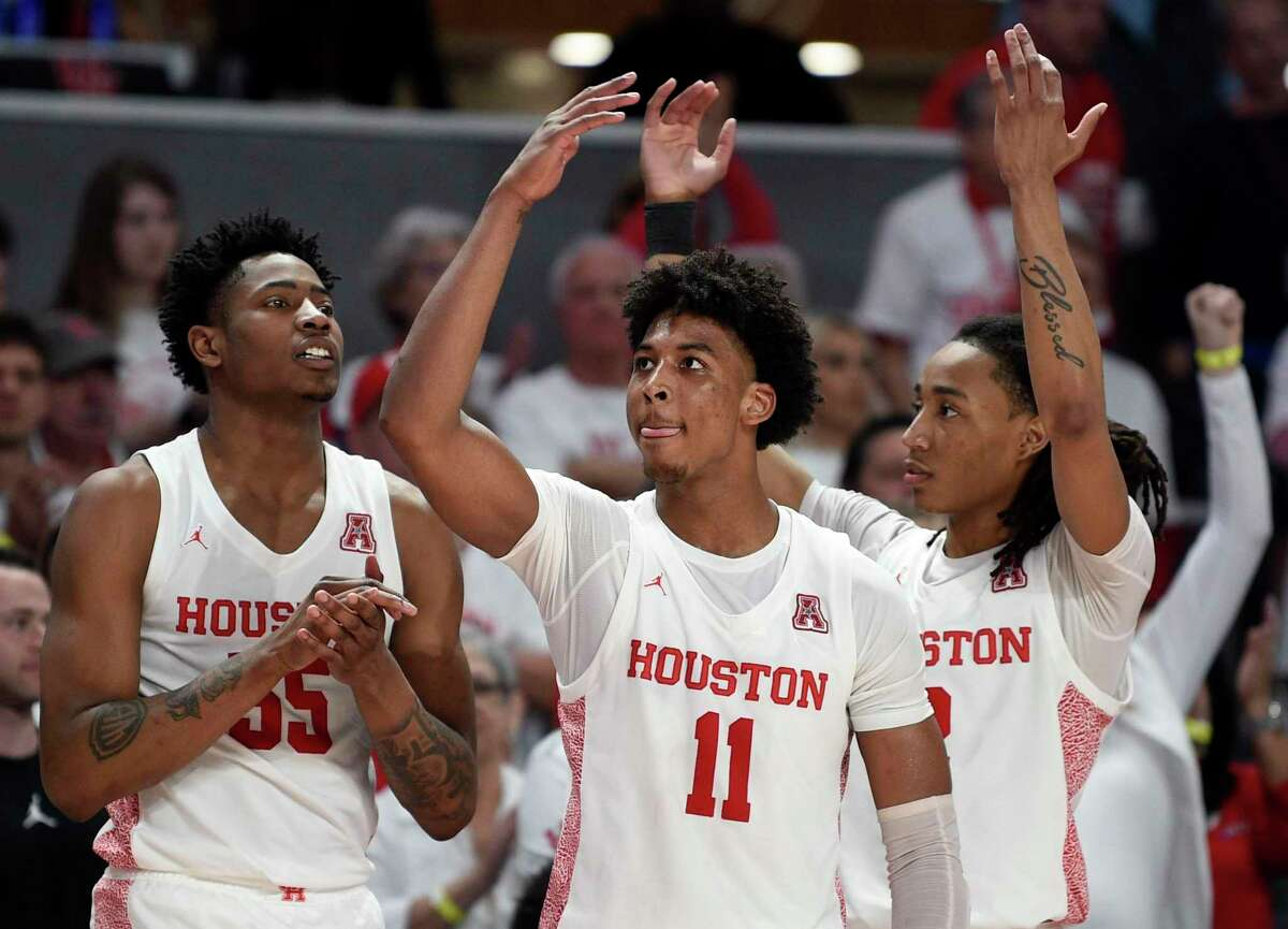 Houston forward Fabian White Jr., left, guard Nate Hinton (11), and guard Caleb Mills celebrate during the final seconds of an NCAA college basketball game against Cincinnati, Sunday, March 1, 2020, in Houston.