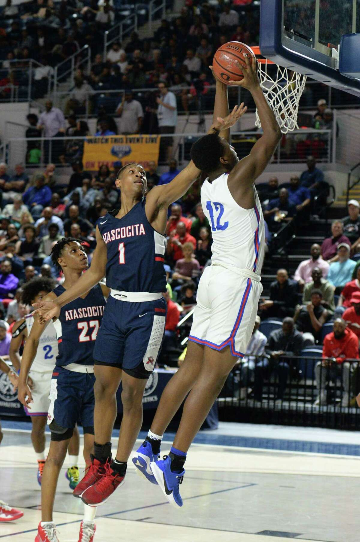 Donovan Green (12) of Dickinson makes a slam dunks past Kaleb Stewart (1) of Atascocita during the fourth quarter of the Boys 6A Region III Quarterfinal basketball game between the Dickinson Gators and the Atascocita Eagles on Tuesday, March 3, 2020 at Delmar Fieldhouse, Houston, TX.