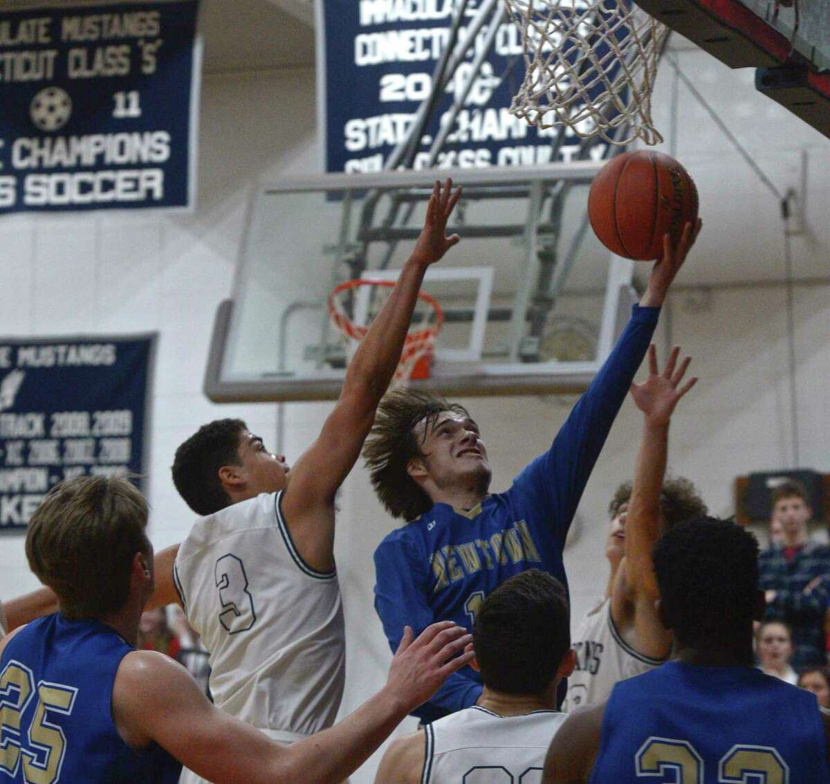 Newtown's Riley Ward (10) drives to the basket past Immaculate's Diego Echavarria (3) in the SWC boys basketball semifinal between No.4 Newtown and No.1 Immaculate, Tuesday night, March 3, 2020, at Immaculate High School, Danbury, Conn.