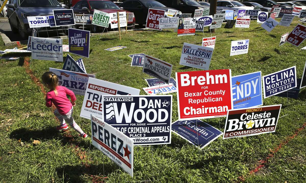 Olivia Pasquini, 3 years-old, runs around political signs at Brook Hollow Library where voters lined up on the last day of early voting.