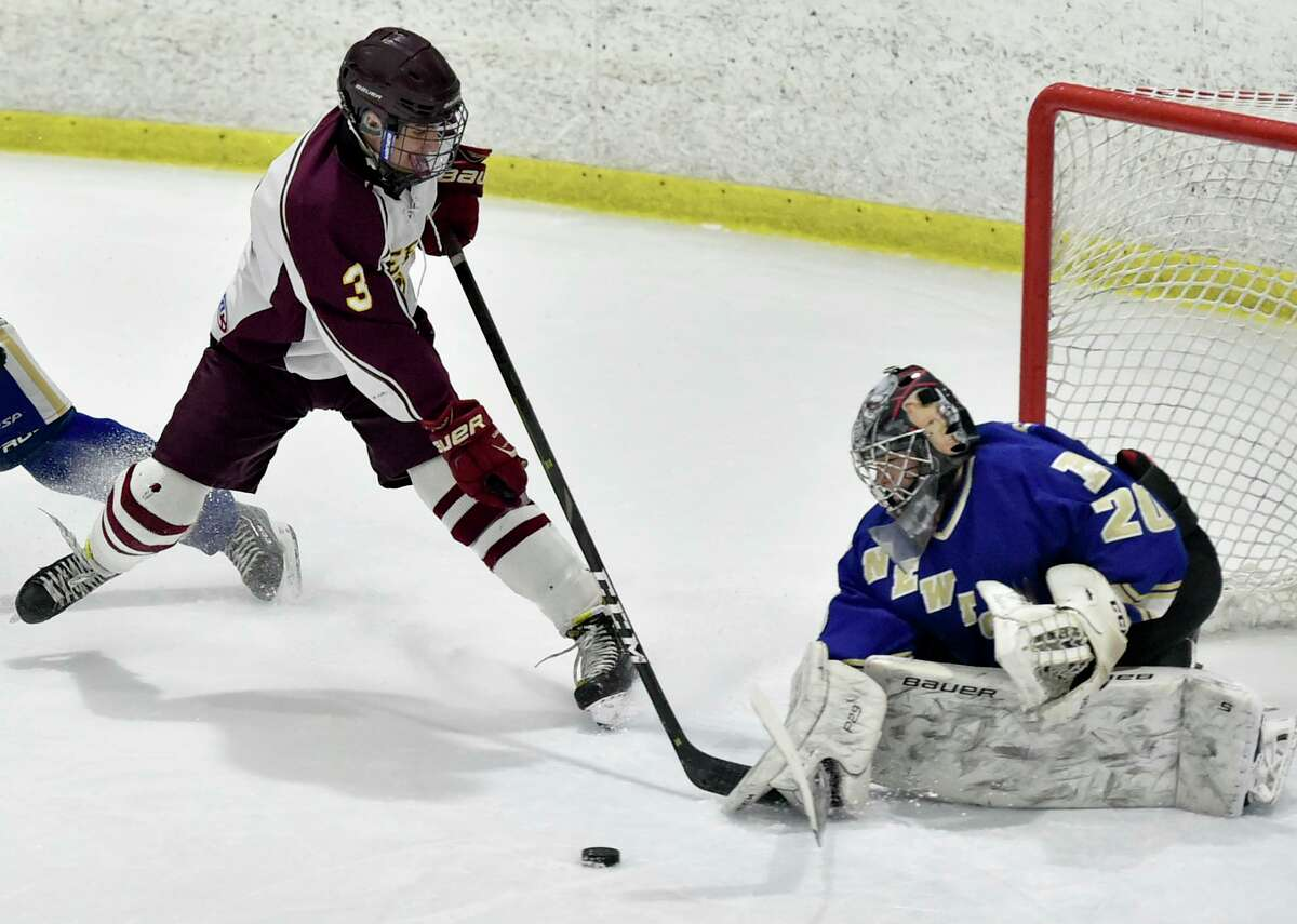Milford, Connecticut - Tuesday, March 04, 2020: Joseph Romano of Sheehan H.S., left, attacks Newtown H.S. goalie Markus Paltauf, right, during the first period of the SCC/SWC 2020 Boys Ice Hockey Division III semifinals Tuesday evening at the Milford Ice Arena in Milford.