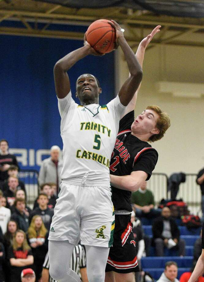 Trinity Catholic's Abdoul Rassoul AbakanHachym (5) puts up a shot under pressure from Fairfield Warde's Dennis Parker in the first half of Tuesday's FCIAC boys basketball semifinal game at Wilton High School. Photo: Matthew Brown / Hearst Connecticut Media / Stamford Advocate