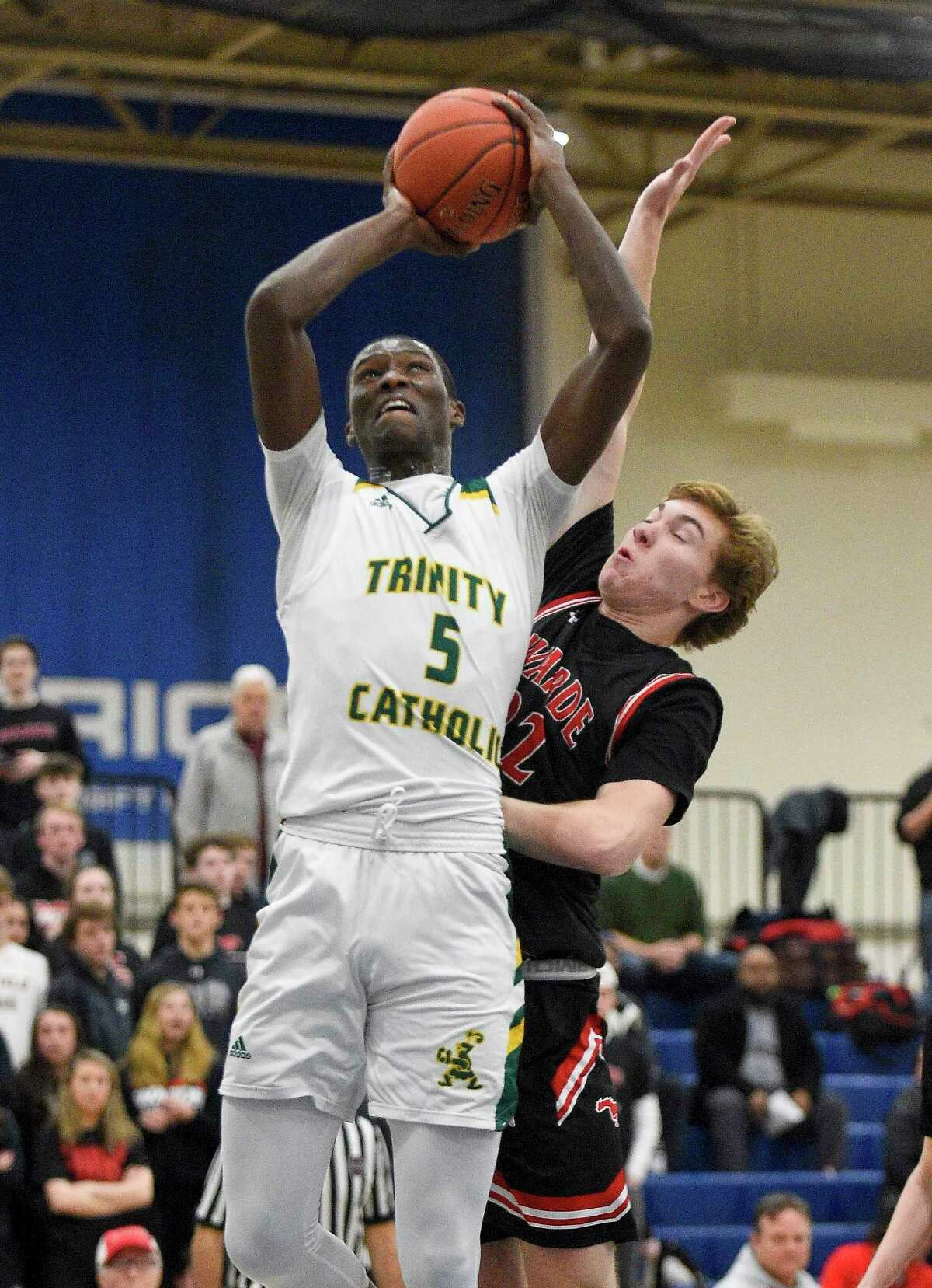 Trinity Catholic's Abdoul Rassoul AbakanHachym (5) puts up a shot under pressure from Fairfield Warde's Dennis Parker in the first half of Tuesday's FCIAC boys basketball semifinal game at Wilton High School.