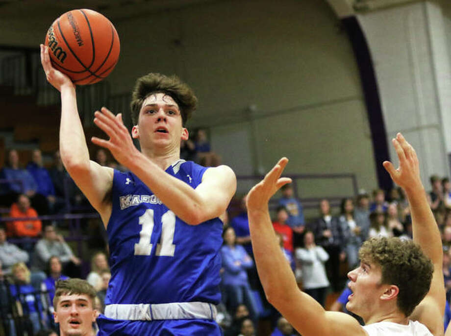 Marquette Catholic's Spencer Cox (11) puts up a shot in the first half Tuesday night against Marshall in the semifinal at the Shelbyville Class 2A Sectional. Cox scored 12 points in the Explorers' 49-37 victory. Photo: Greg Shashack / The Telegraph