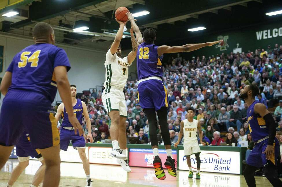 University of Albany's Romani Hansen blocks a shot by University of Vermont's Anthony Lamb during a game on March 3, 2020. (Credit: Brian Jenkins/UVM Athletics)