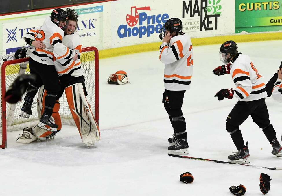Bethlehem's Justin Chenaille embraces goaltender Michael Kurdziolek as other hockey players swarm the net after winning the Division 1 Sectional Championship against Saratoga at Union College in Schenectady, N.Y., Tuesday, Mar. 3, 2020. (Jenn March, Special to the Times Union)