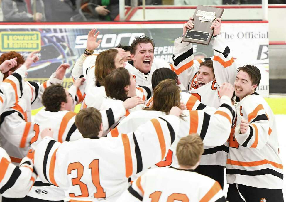 Bethlehem hockey players crowd around Justin Chenaille as he holds the Section II Champions plaque after their victory in the Division 1 Sectional Championship against Saratoga at Union College in Schenectady, N.Y., Tuesday, Mar. 3, 2020. (Jenn March, Special to the Times Union)