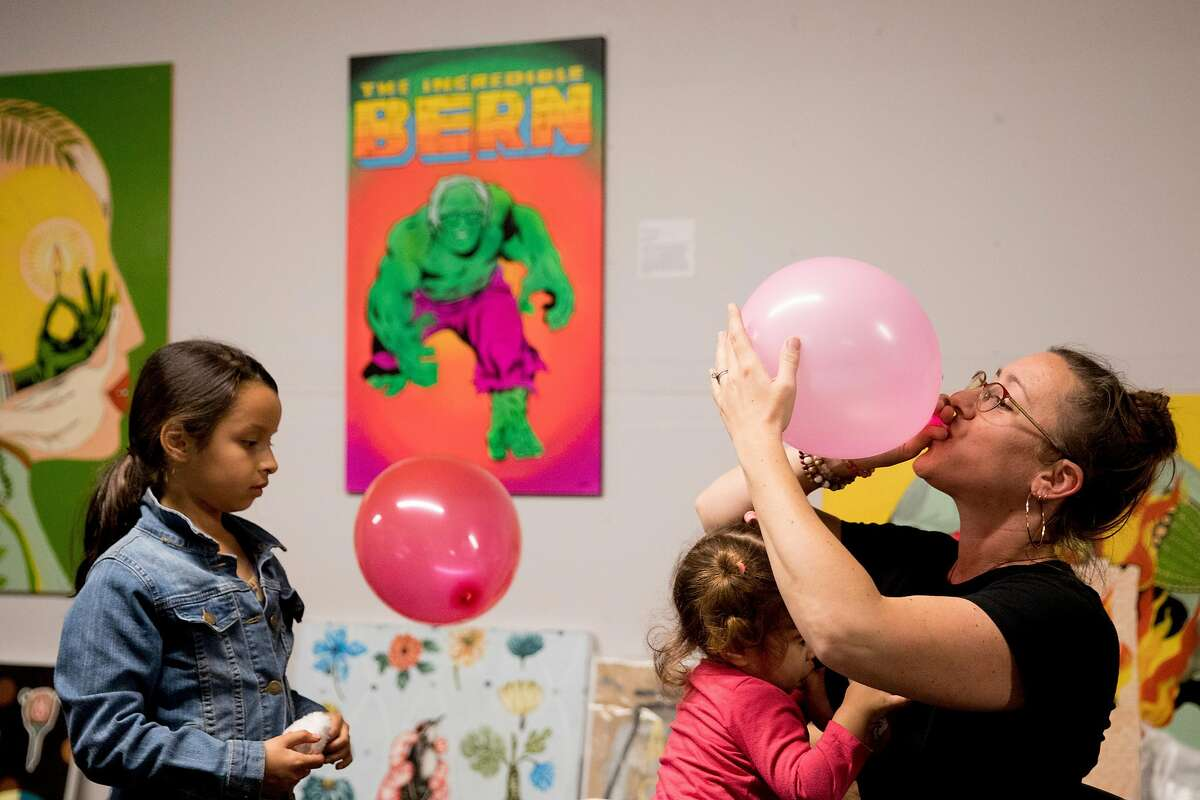 Elisabeth Bolaza with Families for Bernie blows up a balloon for Sailis Batista, 6, while breastfeeding her daughter Naomi, 1, as supporters of Democratic presidential candidate Bernie Sanders gather at the Bernie 2020 campaign headquarters in Oakland, Calif. Tuesday, March 3, 2020 for a election result and karaoke party.