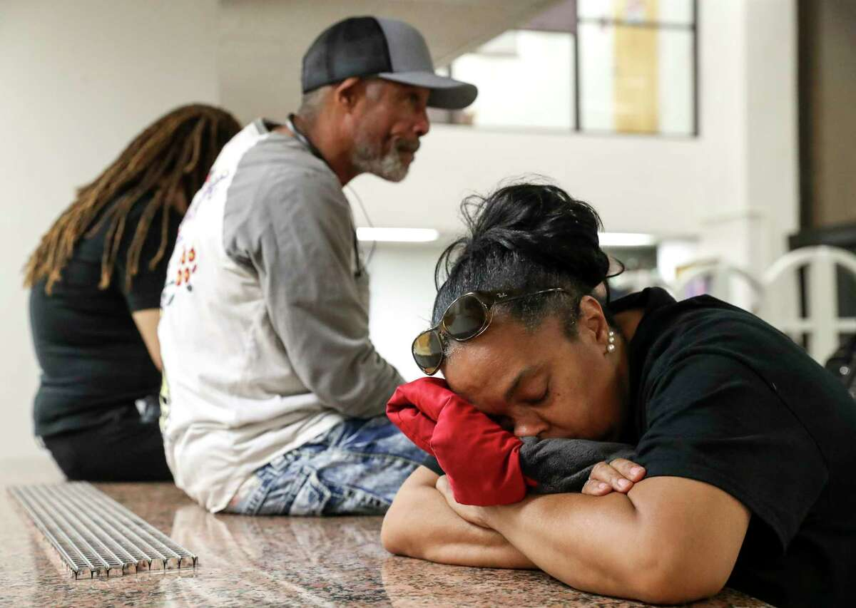 Jacqueline Manuel closes her eyes as she waits in line to vote a little before midnight Tuesday, March 3, 2020, at Texas Southern University in Houston. Manuel said she had been in line for almost five hours. As of midnight, she had not yet voted.
