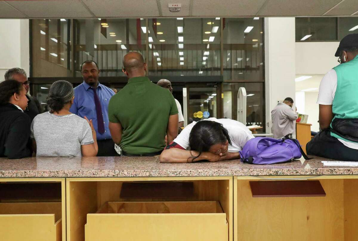 """Whitney Howard, an undergrad student at Texas Southern University, rests her head as she waits in line to vote around midnight Tuesday, March 3, 2020, at Texas Southern University in Houston. As of midnight, she had not yet voted. """"I want to make sure my vote counts,"""" she said."""
