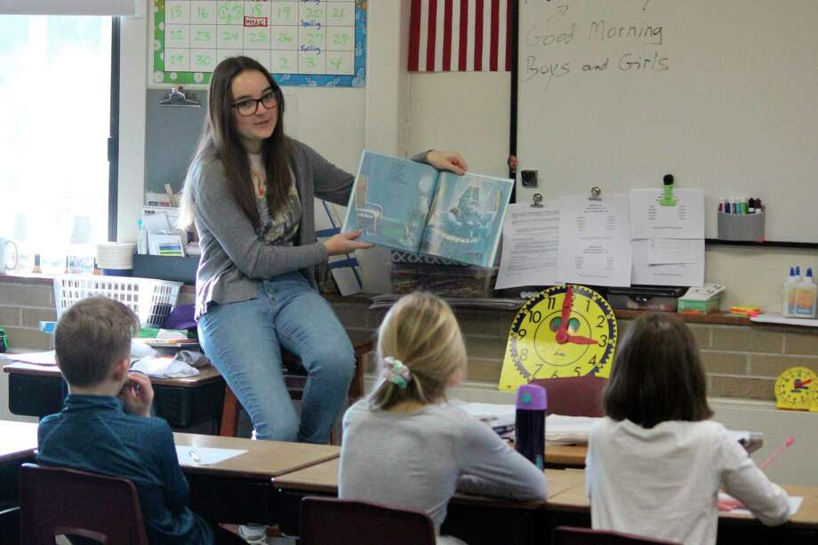 (ABOVE) Nora Pasche spends time reading to third grade students in Derek Jackson's classroom. (LEFT) Amy Robison's first grade students enjoy hearing a story from Ella Larsen. (Photo/Robert Myers)