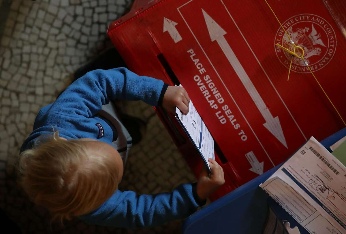 A young boy puts filled out ballots into a box in a polling station at the San Francisco Columbarium & Funeral Home on March 03, 2020 in San Francisco, California. 1,357 Democratic delegates are at stake as voters cast their ballots in 14 states and American Samoa on what is known as Super Tuesday.