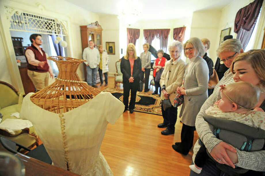 """Tour guide Connor Ashlock tells visitors about wedding traditions through history during the Jersey County Historical Society's """"Tying the Knot: The History of Wedding Traditions"""" event at the historical society's Cheney Mansion in Jerseyville. More than a dozen wedding dresses dating back to the 1800s were on display. Photo: David Blanchette 