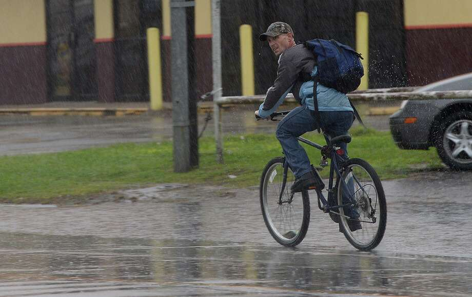 A bicyclist watches out for traffic as he makes his way south on Eleventh Street in Beaumont amid a wave of heavy showers. Thunderstorms producing heavy rainfall and strong winds moved through the region throughout the afternoon and into evening Sunday, causing pooling water on many roadways. Photo taken Sunday, April 7, 2019 Kim Brent/The Enterprise Photo: Kim Brent / The Enterprise / BEN