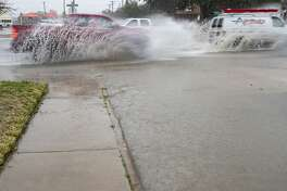 Cars make their way down Big Spring Street this morning as streets around Midland flooded from heavy rains.