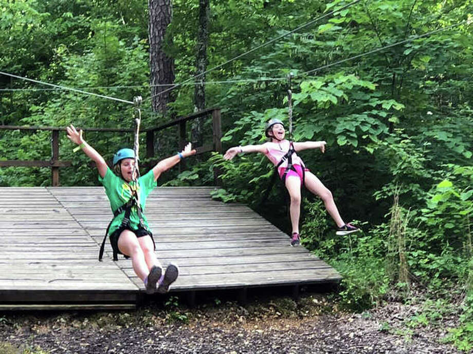 These girls express their joy during ziplining at one of the Girl Scout camps last year. Photo: Hearst File Photo