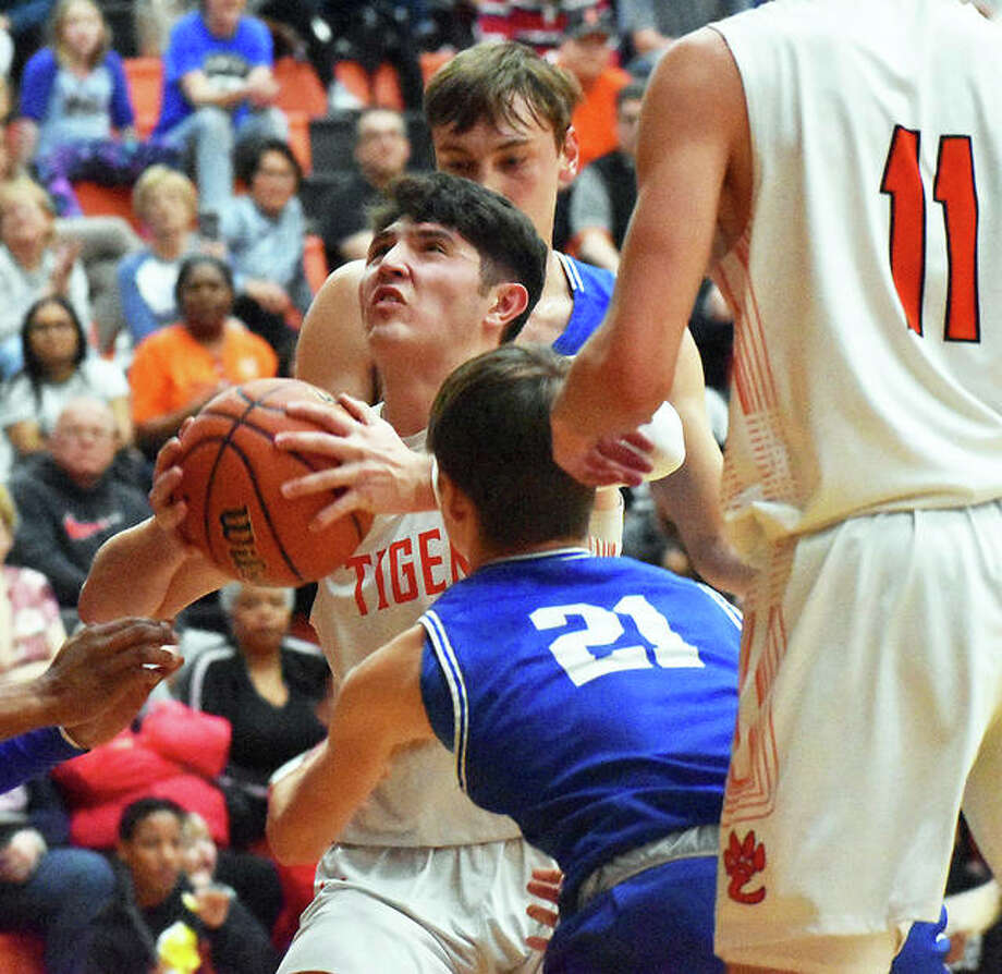 Edwardsville's Nic Hemken looks to the basket between Quincy defenders during Tuesday night's semifinal victory in the Edwardsville Class 4A Regional at Lucco-Jackson Gym. Photo: Matt Kamp / Hearst Midwest