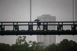 A pedestrian crosses a bridge across Brays Bayou, Wednesday, March 4, 2020, near Hermann Park in Houston.
