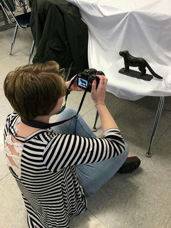 SIUE student Lillian Stevens photographs an artifact brought in by a Liberty Middle School student for the online Madison County historical archives.