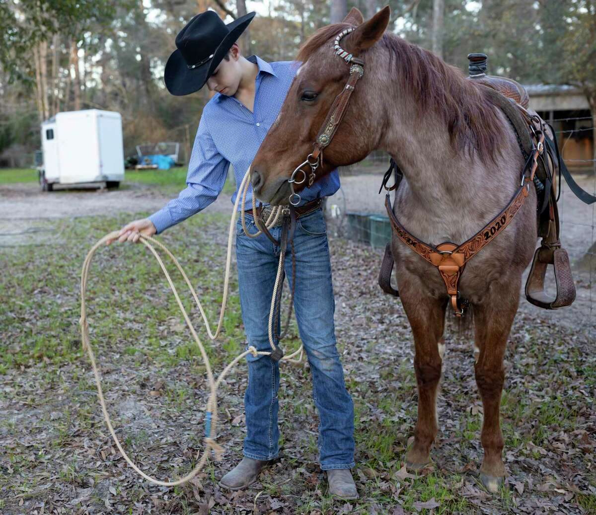 Dean Holtkamp, 14, checks his lasso next to his horse Busters' Prince Roan, in Conroe, Friday, Feb 28, 2020. Holtkamp has qualified to compete at the state finals in tie-down calf roping, chute dogging and ribbon roping.