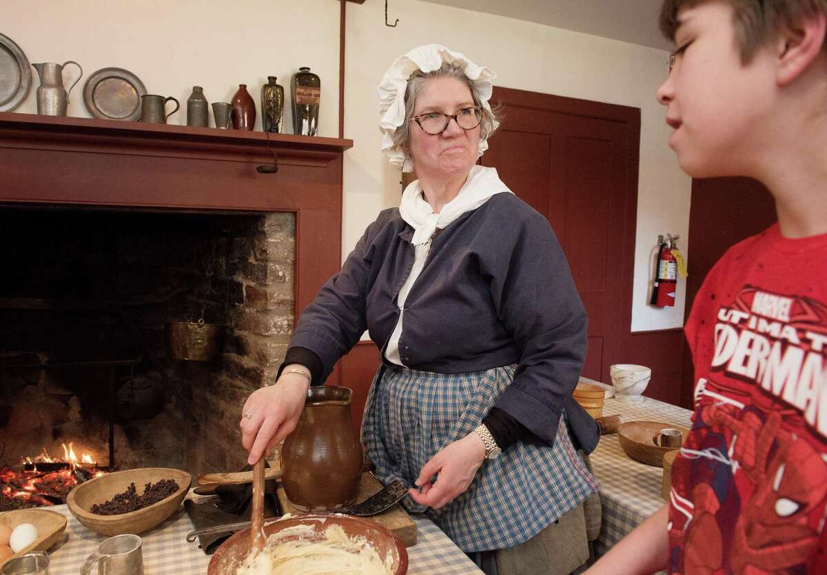 Rebecca Lin of The Wilton Historical Society shows 5th grade Cider Mill students methods of cooking during colonial times. The school group visited the museum on Friday, Feb. 28.