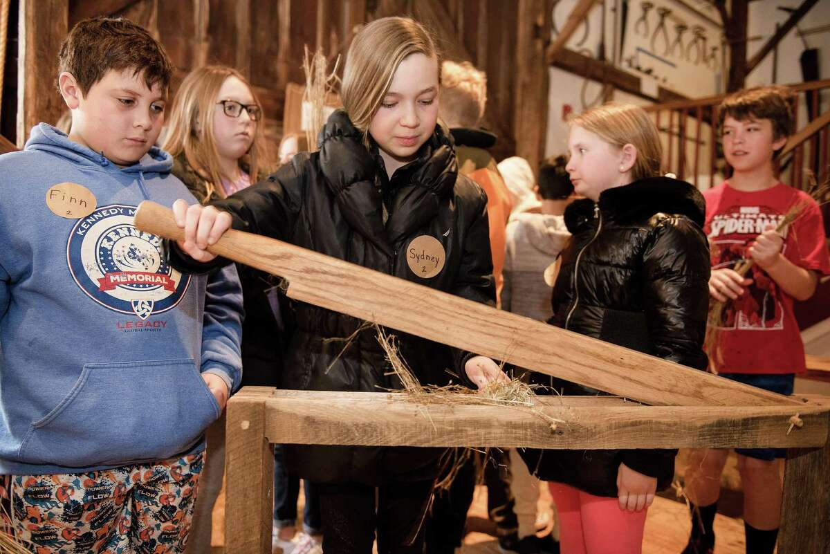 Fifth graders Finn White, Charotte Halliwell, Sydney Fields and Naomi Cronley learn the basics of breaking down flax during a field trip at the Wilton Historical Society.